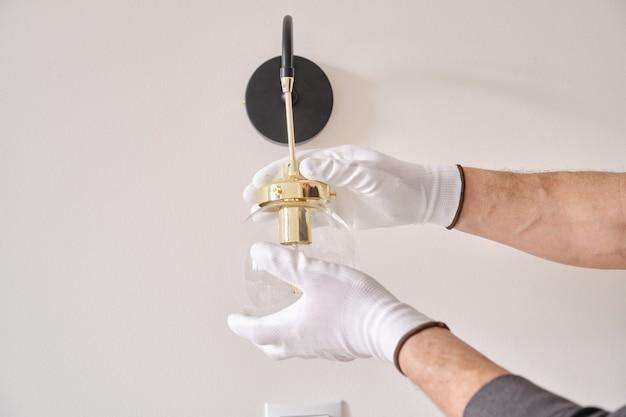 Mani ravvicinate dell'elettricista che installa la lampada da parete.