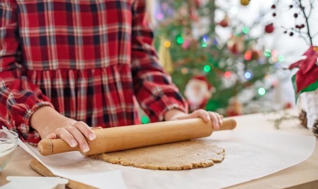 Mani ravvicinate di una ragazza che stende la pasta per i biscotti di pan di zenzero. cottura natalizia.