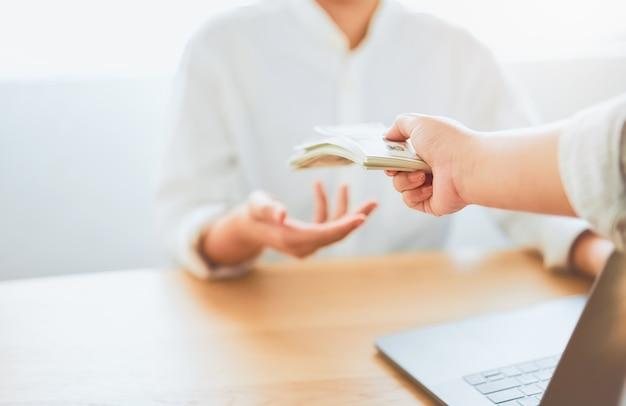 Primo piano delle mani che danno la compensazione di paga del dollaro da lavoro