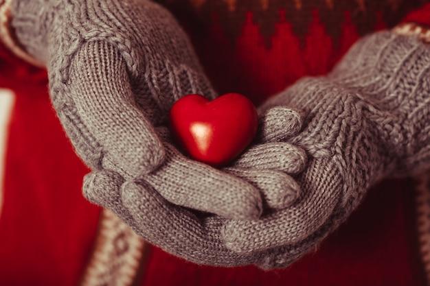 Primo piano delle mani in guanti lavorati a maglia grigi che tengono cuore rosso