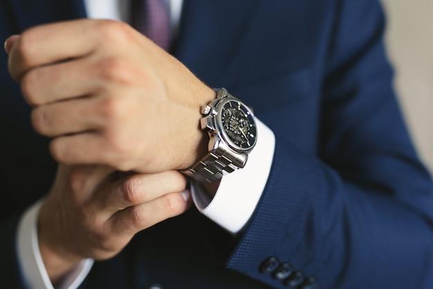 Mani del primo piano dello sposo con un orologio