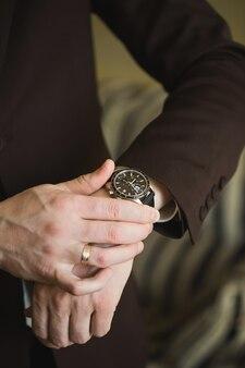 Mani ravvicinate dello sposo con un orologio