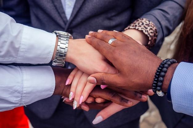 Chiudere le mani di un gruppo di persone multinazionali donna d'affari e uomo d'affari in una stretta di mano di riunione d'affari. concetto di lavoro di squadra