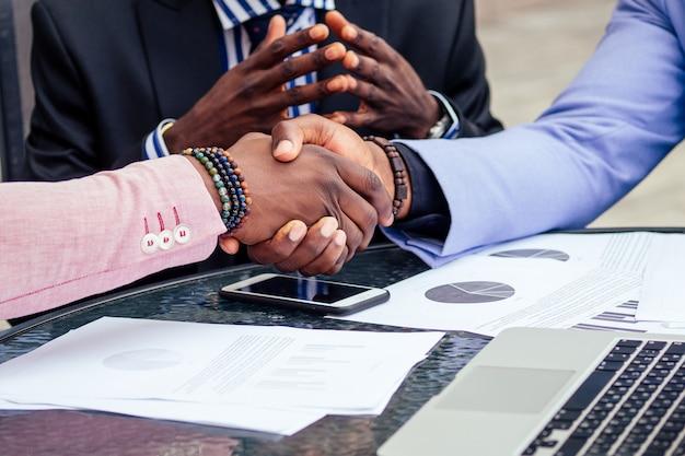 Chiudere le mani del gruppo di tre amici d'affari afroamericani alla moda che si stringono la mano in un caffè estivo all'aperto. concetto di buon affare di successo.