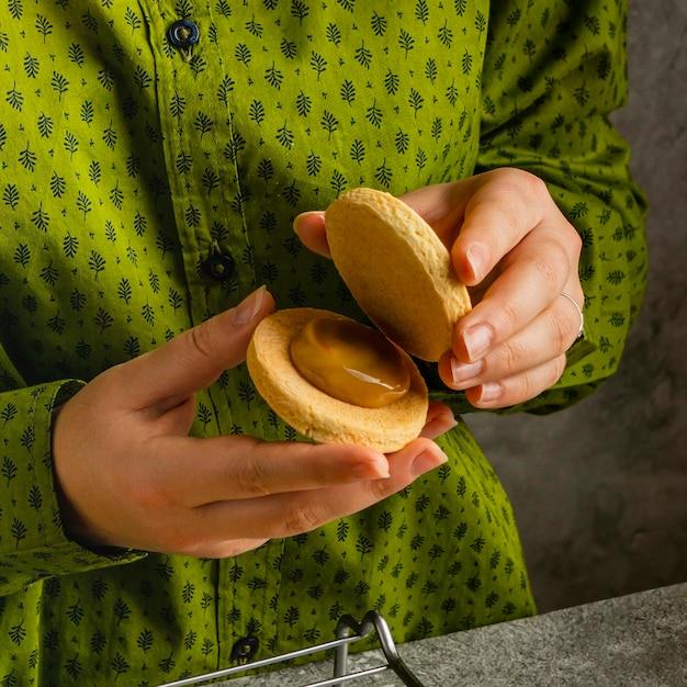 Chiuda in sulle mani che tengono il biscotto con crema