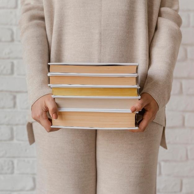 Chiuda sulle mani che tengono la pila di libri
