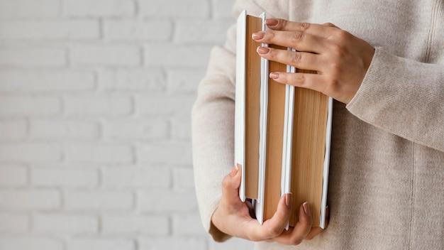 Chiuda sulle mani che tengono i libri con lo spazio della copia