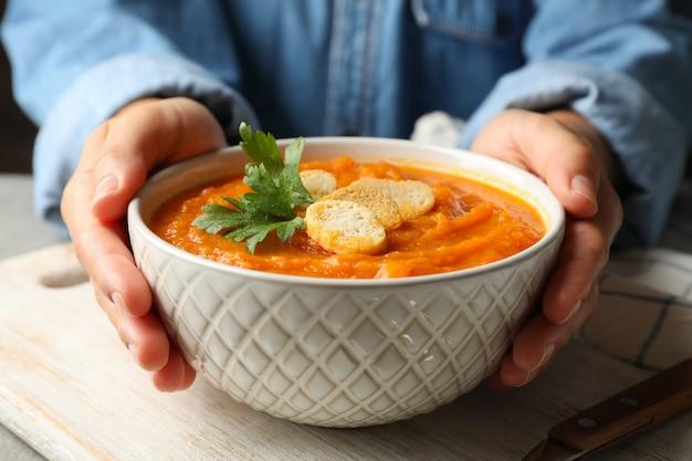 Primo piano sulle mani che tengono ciotola di zuppa di zucca