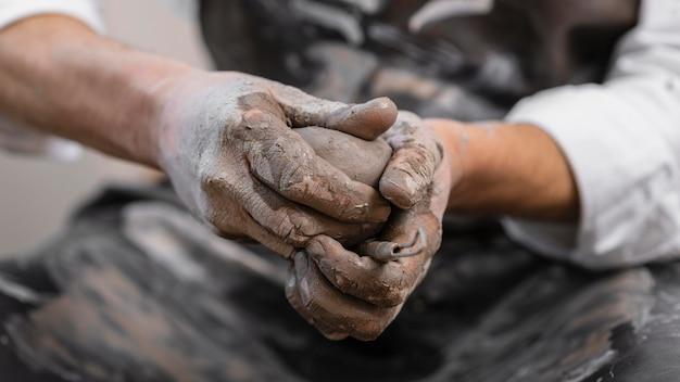 Mani del primo piano che tengono argilla