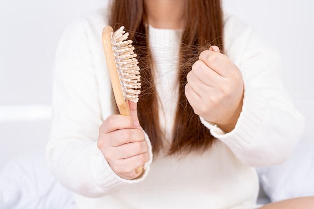 Chiudere le mani tenendo il pettine con il problema della caduta dei capelli