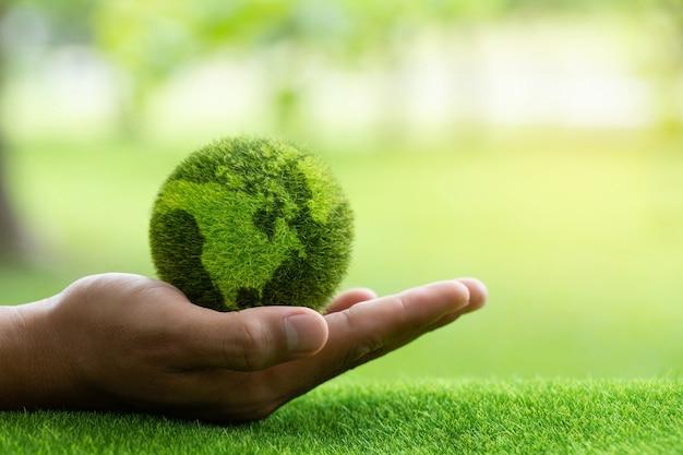 Mani ravvicinate che tengono la terra su sfondo verdeproteggi la naturasalva la terra