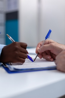 Primo piano delle mani che tengono la penna sui file di documento