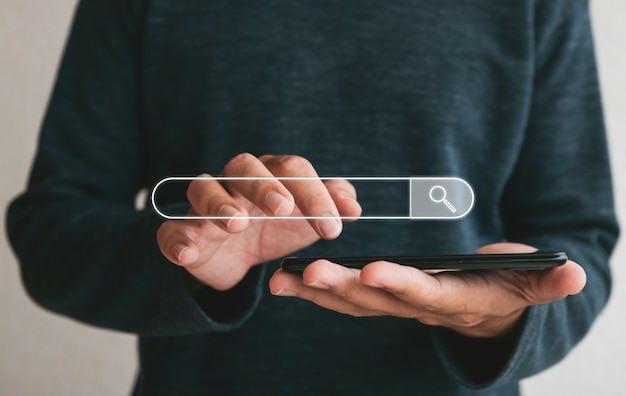 Chiuda sulle mani che tengono smartphone. uomo che lavora con smartphone e con barra di ricerca vuota. ricerca navigazione internet dati informazioni networking concept