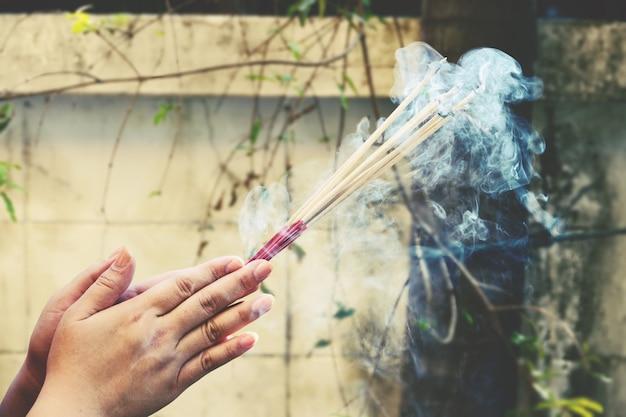 Primo piano delle mani che tengono fumare bastoncini di incenso che brucia