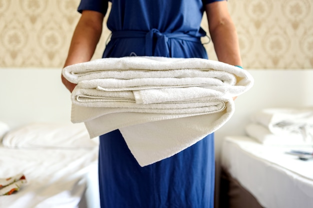 Primo piano delle mani che tengono una pila di asciugamani da bagno bianchi freschi. cliente in una stanza d'albergo.