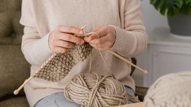 Mani del primo piano che lavorano a maglia all'interno