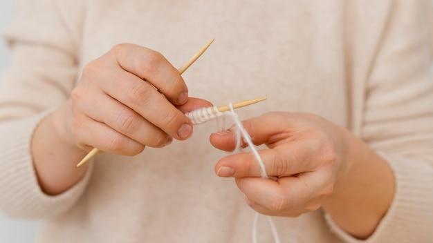 Mani del primo piano che lavorano a maglia con filo bianco Foto Premium