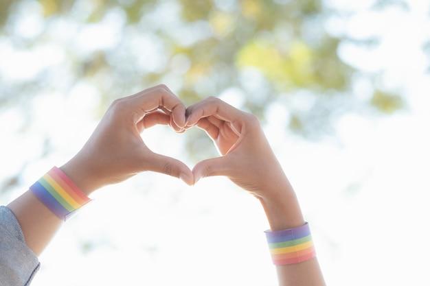 Chiudere le mani delle coppie lgbtq facendo un gesto del cuore.