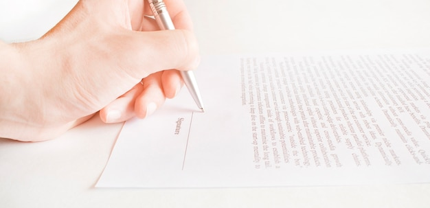 Primo piano delle mani di un uomo che indossa una camicia bianca mentre firma con una penna un documento cartaceo ufficiale o un accordo, posto su un tavolo riflettente nero