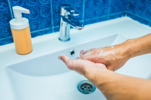 Primo piano delle mani dell'uomo o del giovane adulto caucasico lavandolo con acqua e sapone per prevenire virus e malattie come il coronavirus o il covid-19 - pulirlo a casa nel lavandino del bagno