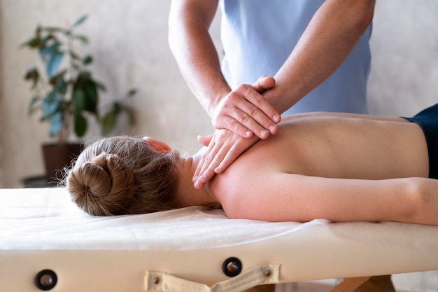 Mani ravvicinate che massaggiano la schiena
