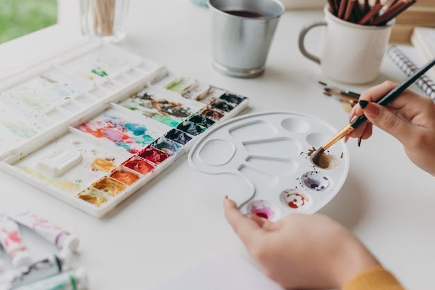 Mani del primo piano che mescolano la vernice