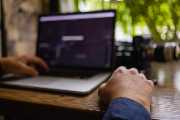 Chiuda sulle mani uomo multitasking utilizzando laptop connessione wifi.