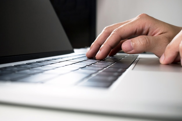 Primo piano, le mani delle persone che stanno stampando con un computer.