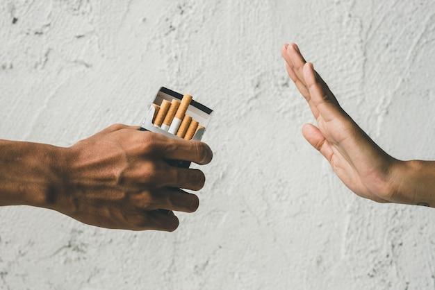 Chiudere le mani della persona che si rifiuta di fumare sigaretta. atteggiamento negativo nei confronti del fumo. smettere di fumare concetto. la mano rifiuta l'offerta di sigarette.