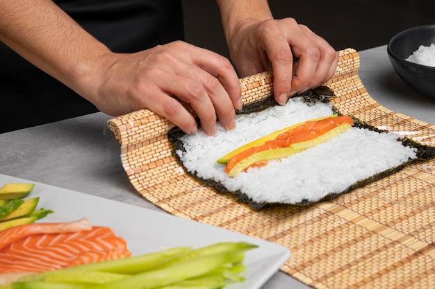 Mani del primo piano che preparano sushi