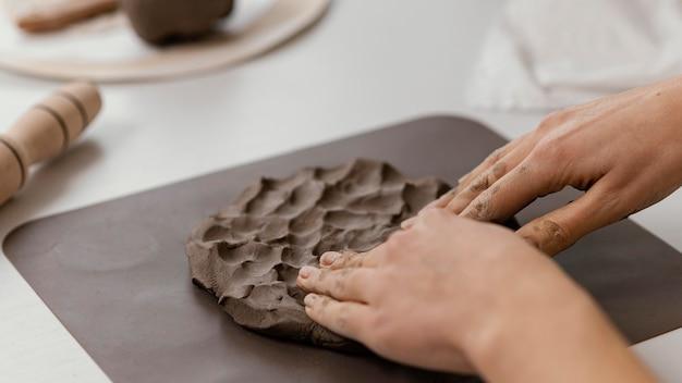 Mani del primo piano che premono argilla