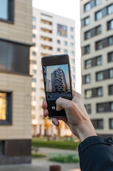 Primo piano delle mani dell'agente immobiliare con il telefono a scattare foto di nuovo edificio residenziale
