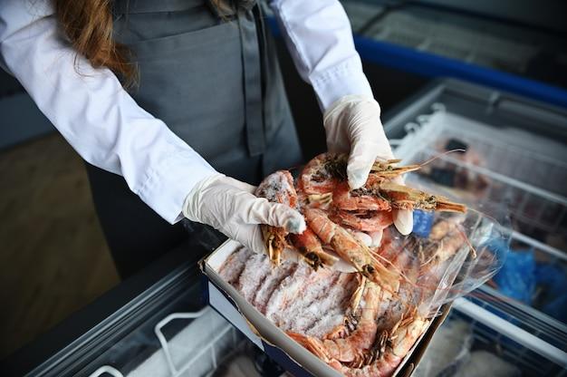 Primo piano delle mani in guanti di gomma di un pescivendolo al negozio di pesce che prende enormi gamberetti congelati fuori dal frigorifero pieno di frutti di mare congelati dell'oceano. veduta dall'alto, vista dall'alto.