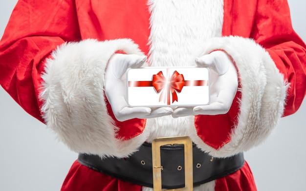 Chiudere le mani di babbo natale che tiene il dispositivo con decorazioni regalo sullo schermo. concetto di saldi invernali, capodanno 2021 e celebrazione del natale, dispositivi e gadget moderni, shopping online.