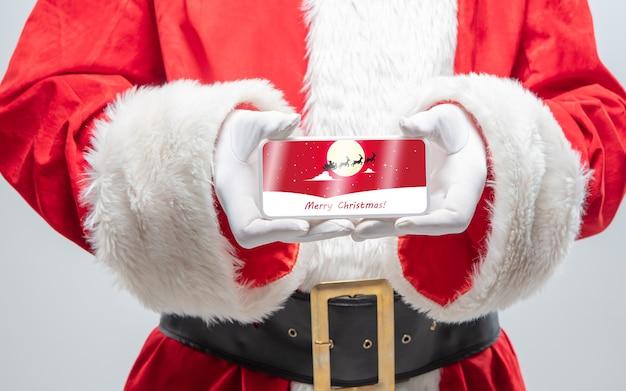 Chiudere le mani di babbo natale che tiene il dispositivo con decorazione da cartolina sullo schermo. concetto di saldi invernali, capodanno 2021 e celebrazione del natale, dispositivi e gadget moderni, shopping online.
