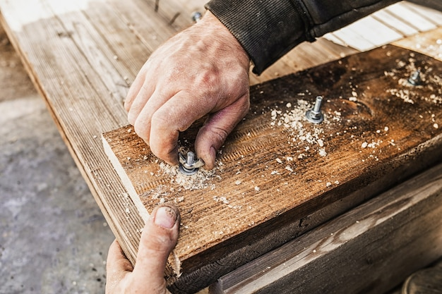 Primo piano di mani avvitando un bullone in una tavola di legno