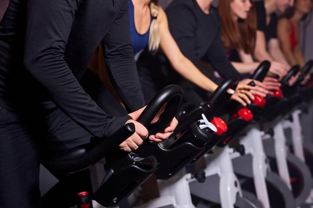 Mani di close-up di persone sportive che guidano cyclette in palestra, foto ritagliata di persone atleta