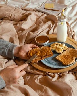 Mani del primo piano che diffondono burro di arachidi sul pane