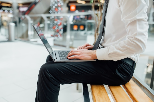 Primo piano delle mani che digitano sulla tastiera del computer portatile nel centro commerciale, vista di profilo, primo piano
