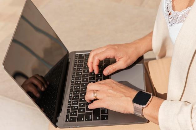 Mani del primo piano che digitano sulla tastiera del computer portatile