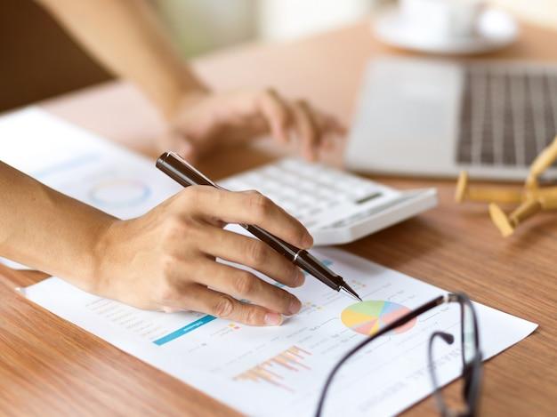 Mani ravvicinate usando la calcolatrice e tenendo la penna, concentrandosi su documenti finanziari su un tavolo di legno