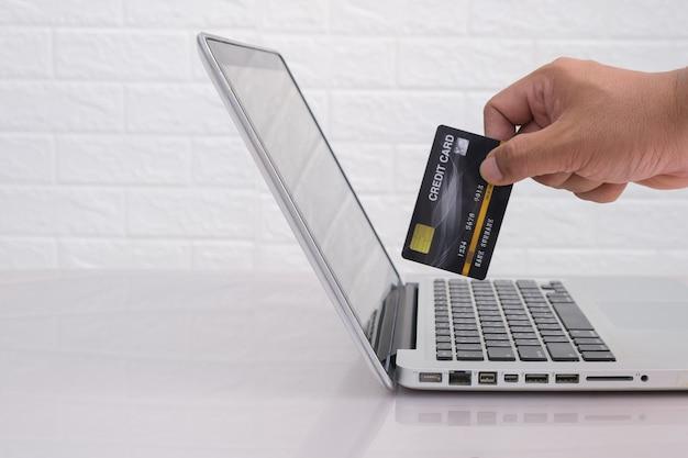 Stretta di mano utilizzando laptop e carta di credito in mano libera dallo spazio della copia. concetto di acquisto / pagamento online.