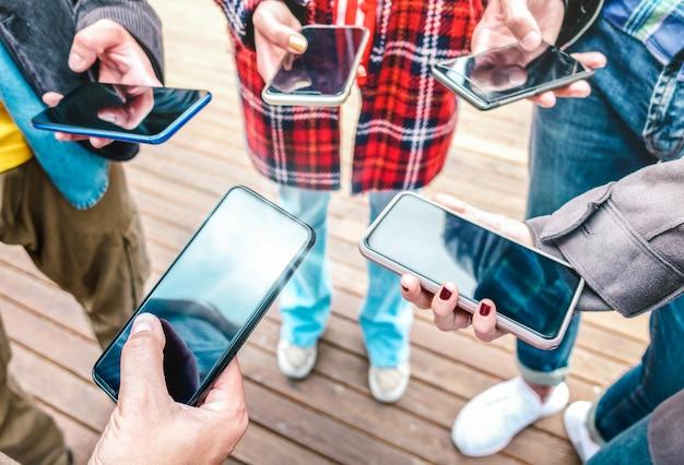 Chiuda in su delle mani utilizzando i telefoni cellulari intelligenti