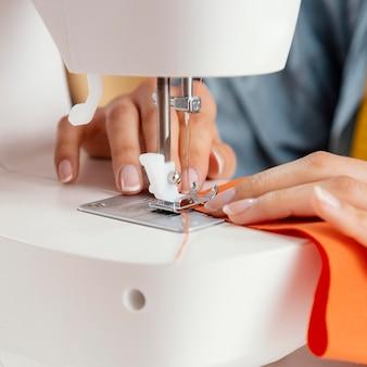 Mani di primo piano utilizzando la macchina da cucire