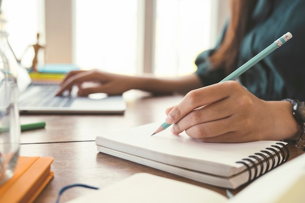 Chiuda sulle mani con scrittura a penna sul taccuino.