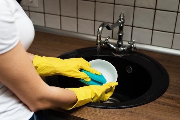 Chiuda sulle mani dei piatti di lavaggio della donna nella cucina. le mani con spugna lavano la piastra sotto l'acqua corrente