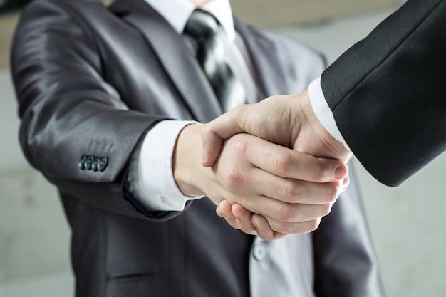 Avvicinamento. stretta di mano uomini d'affari il concetto di cooperazione