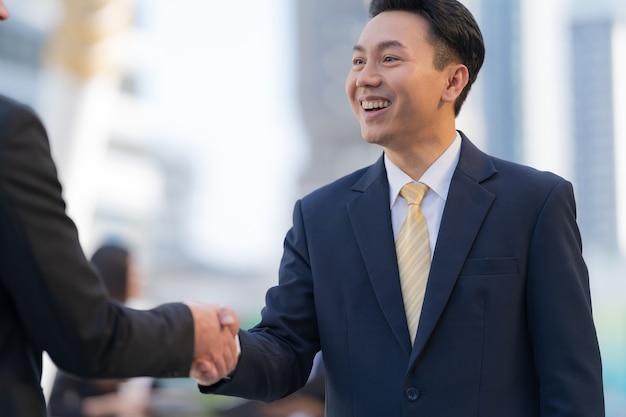 Close up, stretta di mano di due uomini d'affari sullo sfondo di un ufficio moderno, concetto di partnership, stringe la mano per sigillare un affare
