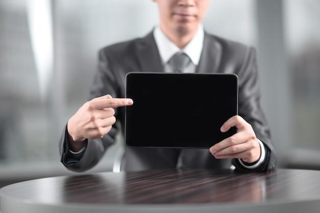 Close up. bell'uomo d'affari che punta allo schermo della tavoletta digitale