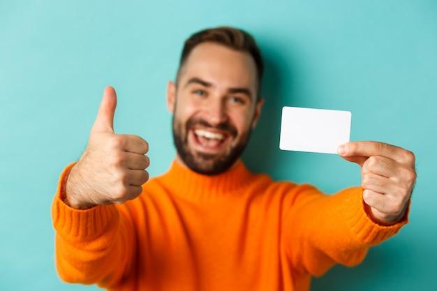 Primo piano di un bell'uomo caucasico che va a fare shopping, mostrando la carta di credito e il pollice in su in segno di approvazione, in piedi su sfondo turchese.